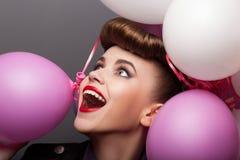 Den gladlynt flickan med luftar ballonger som har gyckel - uttryck royaltyfri fotografi