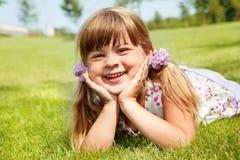 Gladlynt flicka som ligger i sommar arkivbild