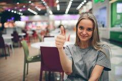 Den gladlynta älskvärda visningen för ung kvinna tummar upp i en matdomstol med en unfocused bakgrund Arkivbild