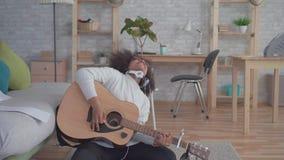 Den gladlynta afrikansk amerikankvinnan med en afro frisyr spelar gitarren som sitter på golvet stock video