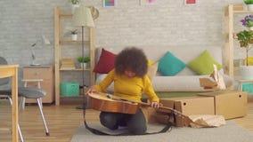 Den gladlynta afrikanska kvinnan med en afro frisyr packar upp en ny gitarr långsam mo stock video