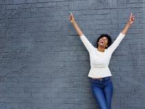 Den gladlynta afrikanska kvinnan med händer lyftte att peka upp Arkivfoton