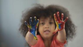 Den gladlynta Afro--amerikanen flickan som har gyckel och uppvisning att målas, gömma i handflatan in i kamera arkivfilmer