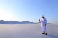 Den gladlynta arabiska manliga turisten kallar vännen på Skype vid cellen och sho Arkivbild