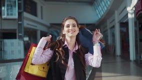 Den gladlynta attraktiva flickan i ett mycket bra lynne i den rosa skjortan och det svarta sleeveless omslaget ler som dansar och stock video