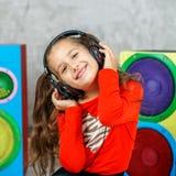 Den gladlynta barnflickan lyssnar till en sång med hörlurar fyrkant C arkivfoton