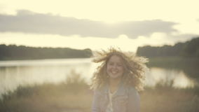Cheerful blonde European girl in a jeans jacket running down the lakeside, turns to camera, smiles and gives a cute kiss Stock Footage