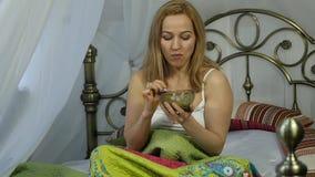 Den gladlynta blonda kvinnaflickan vaknade upp och äta en läcker sallad på en säng, sund frukostultrarapid
