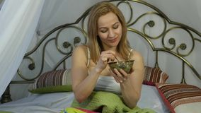 Den gladlynta blonda kvinnan äter en läcker sallad på en säng, den sunda frukosten 4K