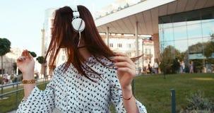 Den gladlynta brunettdamen med nätt leende dansar i utomhus- vit hörlurar längd i fot räknat 4k stock video