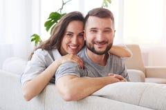 Den gladlynta brunetten och mörker man att krama och att koppla av på soffan Arkivfoto