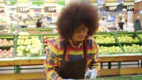 Den gladlynta driftiga kvinnan för supermarketanställdafrikanska amerikanen med en afro frisyr sorterar frukten stock video
