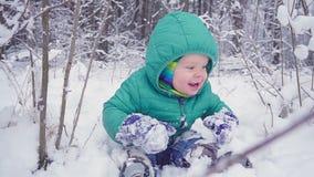 Den gladlynta en årspojken sitter i vinterskogen och skrattar skapat med gimbalen lager videofilmer