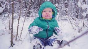 Den gladlynta en årspojken sitter i vinterskogen och skrattar skapat med gimbalen stock video