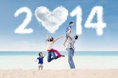 Den gladlynta familjen firar nytt år på stranden Royaltyfri Fotografi