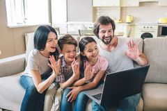 Den gladlynta familjen har bärbara datorn och vinkar med deras händer De talar på skype Det nätta folket ler royaltyfria foton
