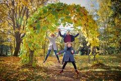 Den gladlynta familjen i hösten parkerar royaltyfria bilder