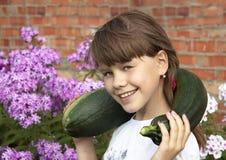 Den gladlynta flickan är i kök-trädgården som samlar zucchinin Royaltyfri Foto