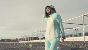 Den gladlynta flickan bär blå kigurumi av enhörningen och hoppar på stranden arkivfilmer