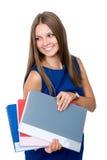 Den gladlynta flickan i en blå klänning med mappar för dokument ser a royaltyfria bilder