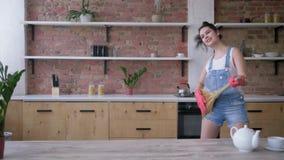 Den gladlynta flickan i handskar spelar på kvasten som en gitarr och en dans lyckligt under att göra ren av köket hemma