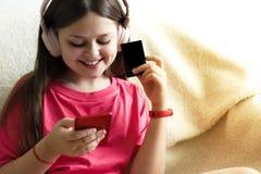 Den gladlynta flickan i rosa hörlurar sitter med en telefon i hennes hand och en kreditkort arkivfoton