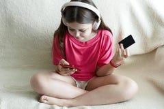 Den gladlynta flickan i rosa hörlurar sitter med en telefon i hennes hand och en kreditkort royaltyfria bilder