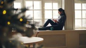 Den gladlynta flickan meddelar med vänner som sitter på fönsterfönsterbräda på dag för nytt år och använder den tryckande på skär stock video