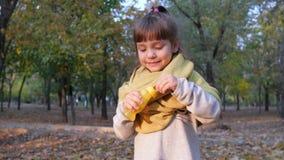 Den gladlynta flickan som har rolig danande, bubblar i ultrarapid på kameran på bakgrundsträd stock video