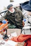 Den gladlynta grå färg-haired mannen som sitter på bänk parkerar in arkivbild