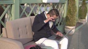 Den gladlynta grabben skriver snabbt på bärbara datorn i kafé stock video