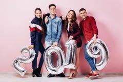 Den gladlynta gruppen av vänner av två flickor och två iklädda stilfulla kläder för grabbar rymmer ballonger i formen av royaltyfria foton