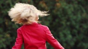 Den gladlynta härliga blonda kvinnan med lockigt hår i det röda omslaget som in vrider, parkerar lager videofilmer