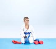 Den gladlynta idrottsman nen i karate poserar nära karatedräkten Royaltyfria Bilder