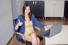Den gladlynta kontor-arbetare visningen tummar upp framme av bärbara datorn royaltyfri foto