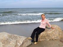 Den gladlynta kvinnan av genomsnittliga år sitter på en stenblock Segla utmed kusten av det baltiska havet Royaltyfri Bild
