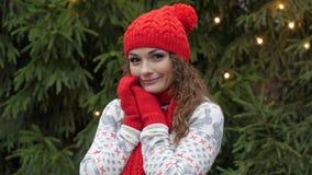 Den gladlynta kvinnan i jultomtenhatt med den röda halsduken och tumvanten är lycklig och banhoppningen mot bakgrunden av julgran Royaltyfri Bild