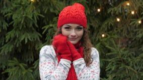 Den gladlynta kvinnan i jultomtenhatt med den röda halsduken och tumvanten är lycklig och banhoppningen mot bakgrunden av julgran Royaltyfri Fotografi