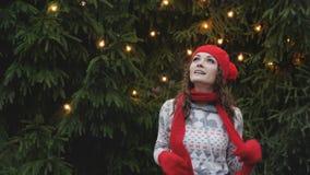 Den gladlynta kvinnan i jultomtenhatt med den röda halsduken och tumvanten är lycklig och banhoppningen mot bakgrunden av julgran Arkivbild