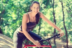 Den gladlynta kvinnan med cykeln parkerar in arkivfoton
