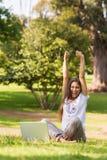 Den gladlynta kvinnan som lyfter händer med bärbara datorn parkerar in Arkivfoto