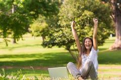 Den gladlynta kvinnan som lyfter händer med bärbara datorn parkerar in Arkivbild