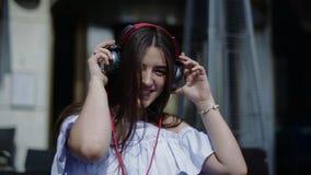 Den gladlynta kvinnan står på den soliga gatan och tycker om att lyssna till musik stock video