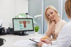 Den gladlynta kvinnliga doktorn ger rådgivning till damen royaltyfri fotografi