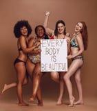 Den gladlynta kvinnliga gruppen med varje kropp är den härliga skylten arkivfoton