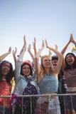 Den gladlynta kvinnlign fläktar mot klar himmel som tycker om musikfestival Arkivfoton