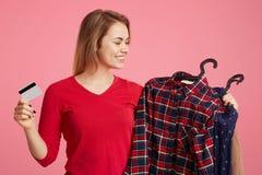 Den gladlynta le kvinnlign gör lyckade köp, blickar på hennes nya kläder, plast- kort för håll som att gå att betala för dräkt, p Royaltyfri Bild