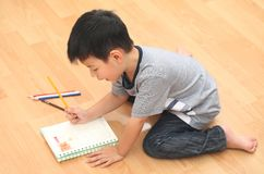 Den gladlynta le pojken som rymmer en ljus färgrik bild, målade c Arkivbild