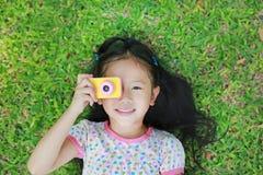 Den gladlynta lilla asiatiska flickan tar fotoet med den färgrika digitala kameran som ligger på grön gräsmattabakgrund royaltyfria foton