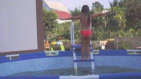 Den gladlynta lilla flickan har gyckel i det friasimbassängen Fps för ultrarapid 240 Barnet är hoppa och spela in stock video